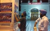 Sikh activists pasting posters on walls