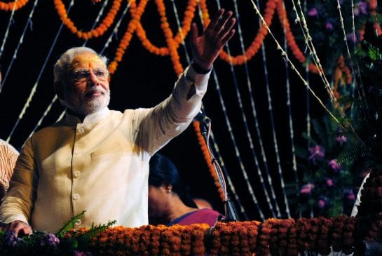 Indian Prime Minister-elect Narendra Modi waves to supporters after performing a religious ritual at the banks of the River Ganges in Varanasi